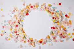 a ideia superior do círculo de confetes coloridos remenda na superfície do branco fotografia de stock royalty free