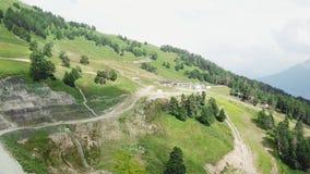 Ideia superior do campo da vila da paisagem e do campo verde, em árvores verdes natureza e em fundo da montanha Vista superior de video estoque