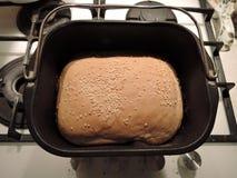 Ideia superior do formulário de um fabricante de pão e de uma crosta do pão cozido fresco com sementes de sésamo imagem de stock royalty free