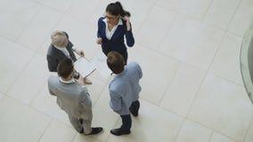 Ideia superior do grupo de executivos nos ternos que discutem gráficos financeiros na entrada do centro de negócios dentro