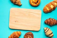 Ideia superior do grupo do pão e da padaria com placa de desbastamento no fundo azul da cor Alimento e conceitos saudáveis imagem de stock royalty free