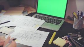 Ideia superior do lugar de trabalho dos desenhistas com a tela da chave do croma do portátil, onde está o projeto de design tirad vídeos de arquivo
