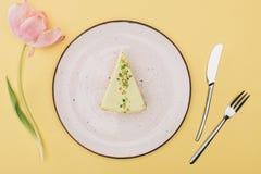Ideia superior do pedaço de bolo na placa, na flor da tulipa e na cutelaria Fotografia de Stock