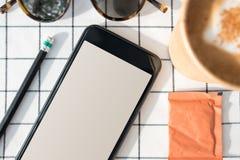 Ideia superior do telefone celular com a tela vazia com copo de café, sungl imagens de stock