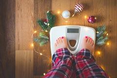 Ideia superior dos pés fêmeas nos pijamas em uma escala branca do peso com decorações do Natal e nas luzes no fundo de madeira imagem de stock royalty free