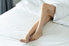 Ideia superior dos pés magros bonitos de uma mulher Pés desencapados de uma jovem mulher que dorme em seu foco macio da cama em c imagem de stock