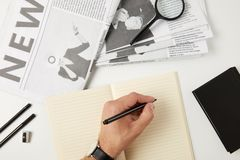 ideia superior parcial da escrita da pessoa no caderno, em jornais, na lupa, no caderno e em materiais de escritório vazios no ci fotos de stock royalty free