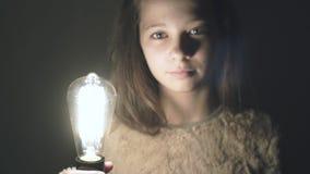 A ideia tem verdadeiro vindo! A ampola na mão de uma moça bonita é iluminada video estoque