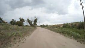 Ideia traseira da condução de carro ao longo de uma estrada de terra rural vídeos de arquivo