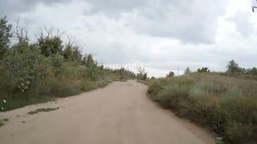 Ideia traseira da condução de carro ao longo de uma estrada de terra rural filme