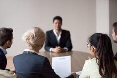 Ideia traseira da hora que escuta o candidato na entrevista de trabalho imagem de stock