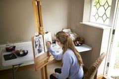 Ideia traseira da imagem adolescente fêmea do desenho de Sitting At Easel do artista do cão da fotografia no carvão vegetal imagem de stock royalty free