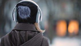 Ideia traseira da música de escuta da mulher irreconhecível nos fones de ouvido na cidade da noite do inverno vídeos de arquivo