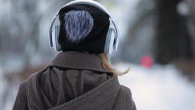 A ideia traseira da música de escuta da mulher irreconhecível veste fones de ouvido na cidade da noite do inverno vídeos de arquivo