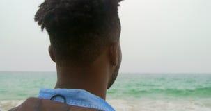 Ideia traseira da posição afro-americano do homem na praia 4k filme