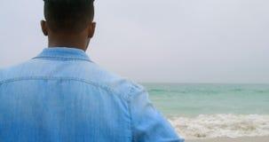 Ideia traseira da posição afro-americano do homem na praia 4k vídeos de arquivo