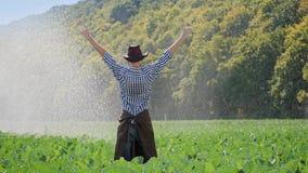 A ideia traseira da posição do fazendeiro na plantação e levanta suas mãos acima filme