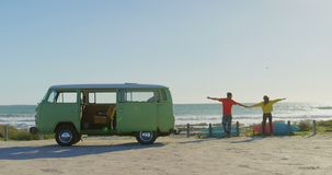 Ideia traseira da posição dos pares com em conjunto na praia em um dia ensolarado 4k filme