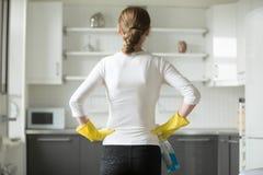 Ideia traseira das mãos da mulher em seus quadris, observando a cozinha fotografia de stock royalty free