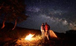 Ideia traseira de aderir-se de duas pessoas entre si olhar no céu estrelado com Via Látea fotos de stock