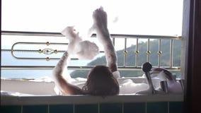 Ideia traseira de banhar a jovem mulher que relaxa na banheira do levantamento da espuma A menina aprecia termas no recurso tropi video estoque