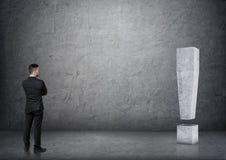 Ideia traseira de marca de exclamação 3D concreta grande tocante do homem de negócios Foto de Stock Royalty Free