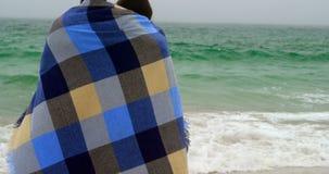 Ideia traseira de pares caucasianos na posição geral na praia 4k vídeos de arquivo