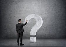 Ideia traseira de ponto de interrogação grande tocante do concreto 3D do homem de negócios Imagem de Stock