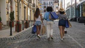 Ideia traseira de um passeio diverso de três fêmeas do cliente vídeos de arquivo