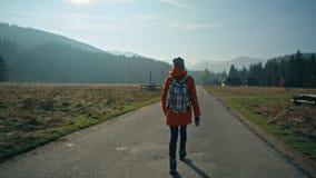 Ideia traseira de uma maneira de menina que anda na estrada bonita no campo na queda filme