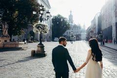 Ideia traseira do busto dos pares felizes lindos do recém-casado que guardam as mãos na rua ensolarada da cidade Fotografia de Stock