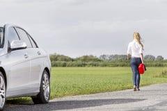 A ideia traseira do comprimento completo do gás levando da mulher pode saindo atrás do carro dividido no campo fotos de stock