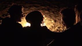 Ideia traseira do grupo de pessoas diverso que senta-se junto pelo fogo tarde na noite e que abraça-se cheerful filme