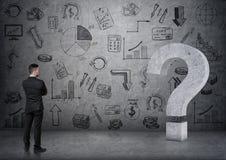 A ideia traseira do ponto de interrogação 3D concreto grande tocante do homem de negócios no backgound com negócio rabisca Foto de Stock Royalty Free