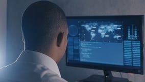 Ideia traseira do programador do homem no funcionamento branco da camisa no computador no centro de dados vídeos de arquivo