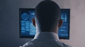 Ideia traseira do programador do homem no funcionamento branco da camisa no computador no centro de dados filme