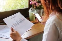A ideia traseira do telefone celular com calculadora app é usada pelas mãos da mulher de negócio em seu escritório Profundidade d Imagens de Stock Royalty Free