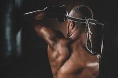 Ideia traseira do treinamento tailandês do atleta de Muay no encaixotamento tailandês com saco de perfuração Foto de Stock