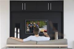 Ideia traseira dos canais em mudança do homem do meados de-adulto com controlo a distância da televisão na sala de visitas imagens de stock royalty free