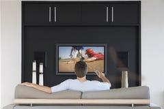 Ideia traseira dos canais em mudança do homem do meados de-adulto com controlo a distância da televisão na sala de visitas imagens de stock