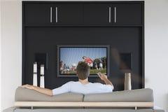 Ideia traseira dos canais em mudança do homem do meados de-adulto com controlo a distância da televisão na sala de visitas fotografia de stock royalty free