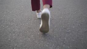 Ideia traseira dos pés da mulher s que andam em uma estrada video estoque