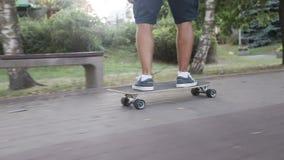 Ideia traseira dos pés do skate da equitação do homem no dia ensolarado vídeos de arquivo