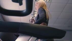 Ideia traseira dos pés fêmeas que andam e que correm na escada rolante no gym, treinamento da mulher filme