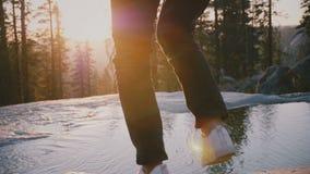 Ideia traseira dos pés fêmeas que pisam com cuidado sobre o córrego bonito pequeno da água em uma rocha no movimento lento do par filme