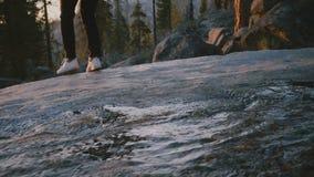 Ideia traseira dos pés fêmeas que saltam sobre um córrego pequeno da água, menina que anda acima para balançar a borda no movimen filme