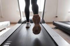 Ideia traseira dos p?s f?meas A mulher atlética no sportswear preto nas sapatilhas brancas corre em uma escada rolante em um gym  fotografia de stock royalty free