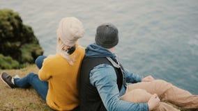 Ideia traseira dos pares à moda novos que sentam-se na borda do penhasco e que olham no mar, apreciando a paisagem bonita vídeos de arquivo