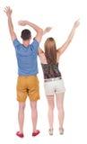 Ideia traseira dos pares alegres que comemoram as mãos da vitória acima Fotografia de Stock Royalty Free