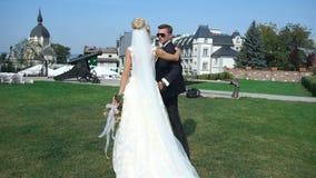 Ideia traseira dos pares atrativos novos de recém-casados que guardam as mãos ao andar ao longo do jardim perto do castelo vídeos de arquivo